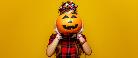 Colorful halloween. young woman in Mexican style halloween costume isolated on yellow holding jack-o-lantern pumpkin in the front of face Stock Photo
