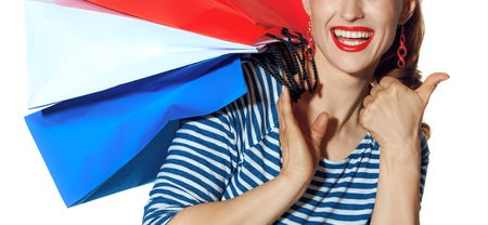Shopping. The French way. Closeup on smiling trendy fashion-monger with shopping bags of the colours of the French flag isolated on white background showing thumbs up