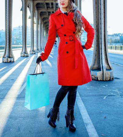 Bright in Paris. Closeup on elegant tourist woman in red trench coat on Pont de Bir-Hakeim bridge in Paris with shopping bag