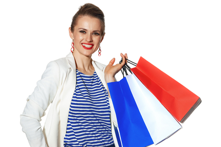 Luxury Shopping. The French way. happy modern woman in white jacket isolated on white with shopping bags painted in the color of the French flag Stock Photo