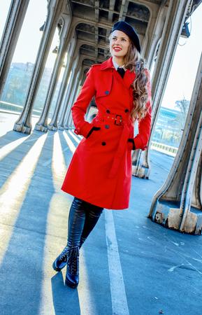 Bright in Paris. happy young tourist woman in red trench coat on Pont de Bir-Hakeim bridge in Paris looking into the distance