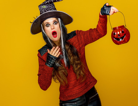 Colorful halloween. surprised young woman in halloween witch costume isolated on yellow background holding jack-o-lantern