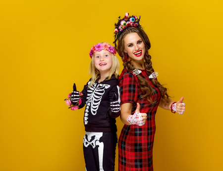 Colorful halloween. happy modern mother and child in Mexican style halloween costume isolated on yellow background showing thumbs up Stock Photo
