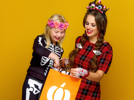 Colorful halloween. happy modern mother and child in Mexican style halloween costume isolated on yellow looking at Halloween shopping bag