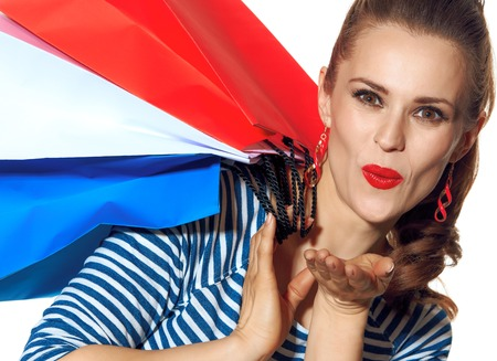 Shopping. The French way. happy young woman with shopping bags of the colours of the French flag isolated on white background blowing air kiss