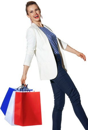 Luxury Shopping. The French way. smiling young woman in white jacket isolated on white with shopping bags painted in the color of the French flag walking