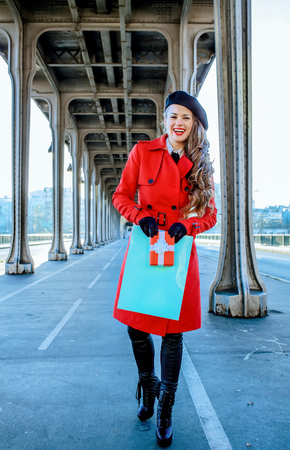 Bright in Paris. Full length portrait of happy trendy tourist woman in red trench coat on Pont de Bir-Hakeim bridge in Paris with shopping bag and Christmas present box