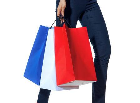 Shopping. The French way. Closeup on modern fashion-monger with shopping bags of the colours of the French flag isolated on white walking Standard-Bild - 108416766
