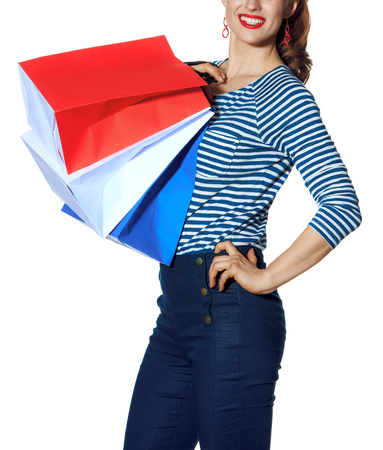 Shopping. The French way. Closeup on smiling stylish fashion-monger with shopping bags of the colours of the French flag isolated on white background