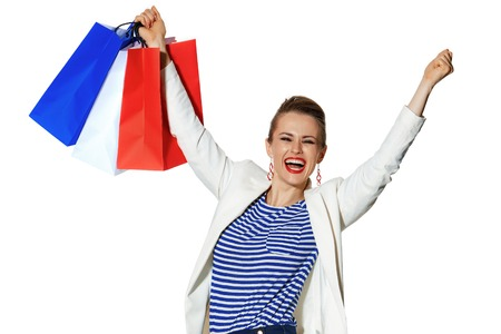 Luxury Shopping. The French way. smiling modern woman in white jacket with shopping bags isolated on white background rejoicing Stock Photo