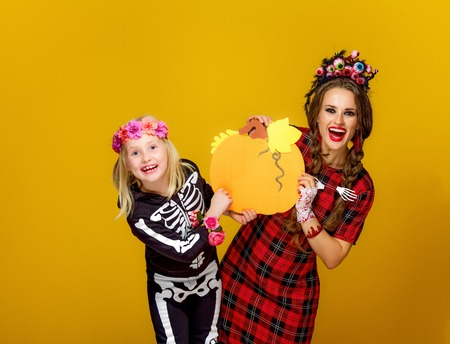 Colorful halloween. happy modern mother and child in Mexican style halloween costume on yellow background showing pumpkin Banco de Imagens