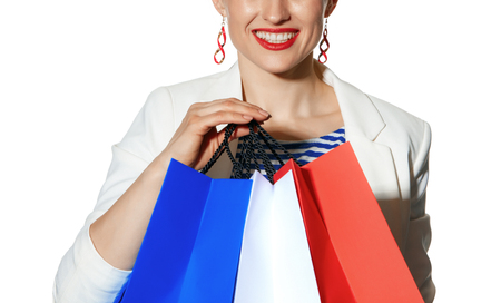 Luxury Shopping. The French way. happy young woman in white jacket isolated on white background with shopping bags painted in the color of the French flag Stock Photo