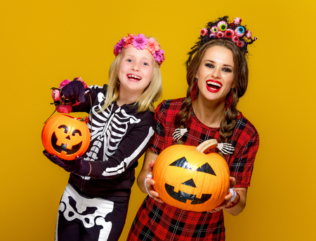 Colorful halloween. smiling modern mother and daughter in Mexican style halloween costume on yellow background showing jack-o-lantern pumpkins Banco de Imagens
