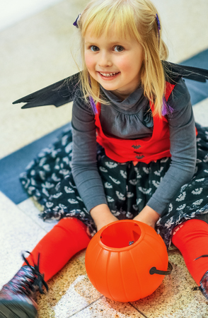 Trick or Treat. happy modern child in bat costume on Halloween at the mall sitting with pumpkin Jack O'Lantern basket Stock Photo