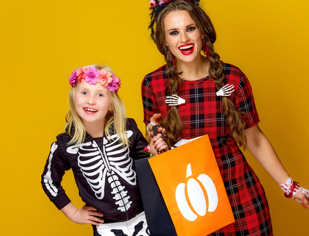 Colorful halloween. smiling modern mother and child in Mexican style halloween costume isolated on yellow showing shopping bags