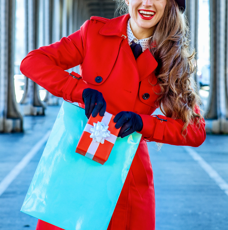 Bright in Paris. Closeup on happy young tourist woman in red trench coat on Pont de Bir-Hakeim bridge in Paris showing shopping bag and Christmas present box