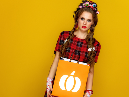 Colorful halloween. modern woman in Mexican style halloween costume on yellow background with shopping bag