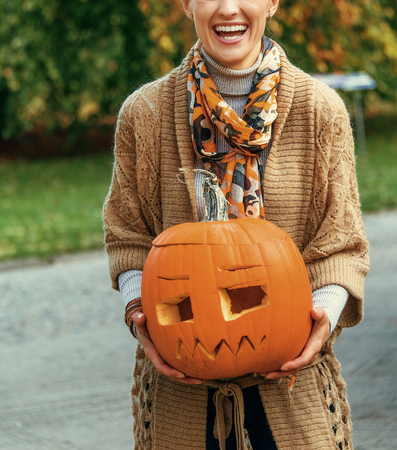 Trick or Treat. smiling modern woman on Halloween outdoors showing carved big pumpkin Stock Photo