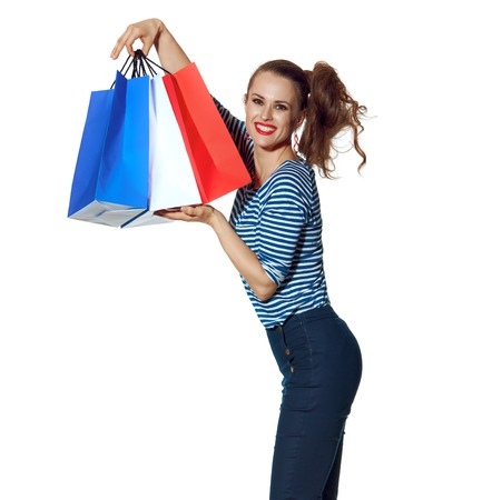 Shopping. The French way. happy stylish fashion-monger showing shopping bags of the colours of the French flag isolated on white Standard-Bild - 108415625