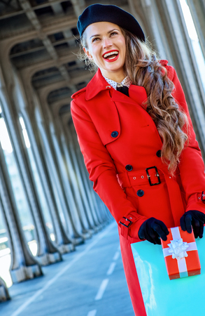 Bright in Paris. smiling trendy tourist woman in red trench coat on Pont de Bir-Hakeim bridge in Paris with shopping bag and Christmas present box 스톡 콘텐츠