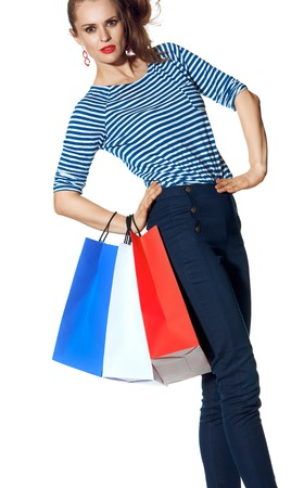 Shopping. The French way. modern woman with shopping bags of the colours of the French flag isolated on white background
