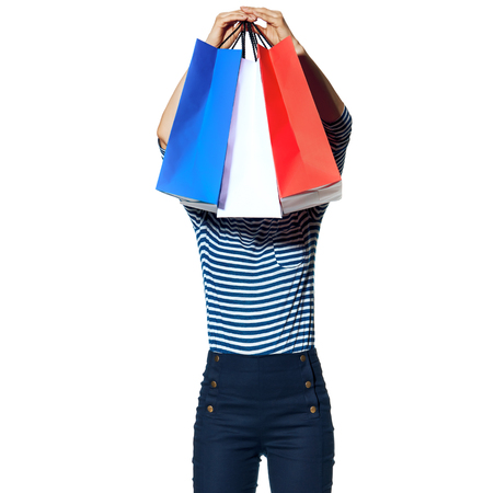 Shopping. The French way. young fashion-monger holding in the front of head shopping bags of the colours of the French flag isolated on white Standard-Bild - 108417104