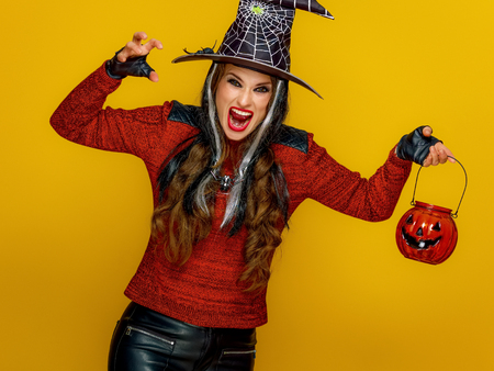 Colorful halloween. modern woman in halloween witch costume on yellow background with jack-o-lantern frightening Stock Photo
