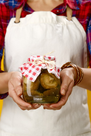 Healthy food to your table. Closeup on modern woman cook wearing apron isolated on yellow showing a jar of marinated mushrooms 版權商用圖片