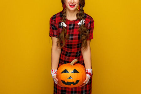 Colorful halloween. happy young woman in Mexican style halloween costume on yellow background holding jack-o-lantern pumpkin Stock Photo