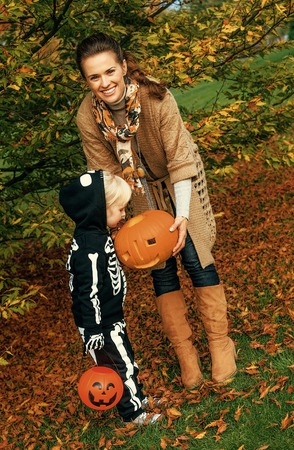 Trick or Treat. happy modern mother and child outdoors on Halloween playing