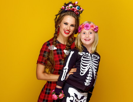 Colorful halloween. smiling modern mother and child in Mexican style halloween costume on yellow background
