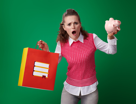 stressed modern student woman in a red waistcoat with shopping bag with books and piggy bank on green background Stock Photo