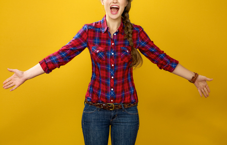 Healthy food to your table. Closeup on happy young woman farmer in checkered shirt on yellow background excited Stock Photo