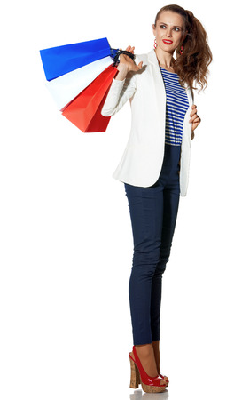Luxury Shopping. The French way. Full length portrait of smiling stylish woman in white jacket isolated on white with shopping bags painted in the color of the French flag looking at copy space
