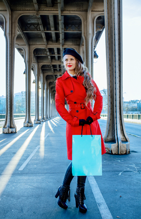 Bright in Paris. Full length portrait of happy young woman in red trench coat on Pont de Bir-Hakeim bridge in Paris with shopping bag  looking into the distance