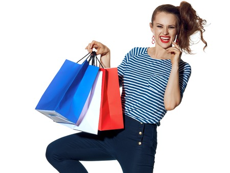 Shopping. The French way. cheerful stylish fashion-monger with shopping bags of the colours of the French flag isolated on white posing Stockfoto