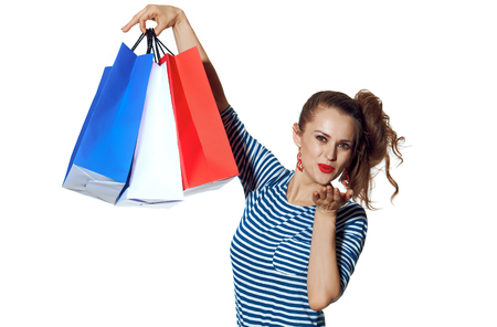 Shopping. The French way. smiling trendy woman with shopping bags of the colours of the French flag isolated on white blowing air kiss