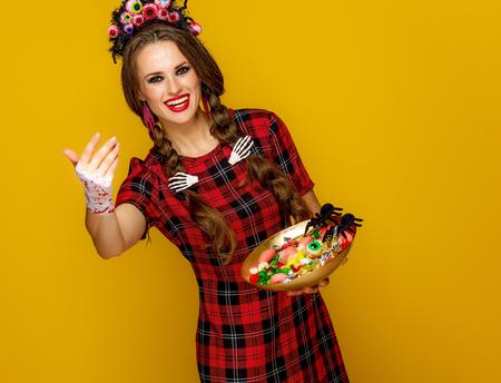 Kleurrijk Halloween. lachende moderne vrouw in Mexicaanse stijl halloween kostuum op gele achtergrond met plaat van Halloween snoepjes bellen om dichterbij te komen
