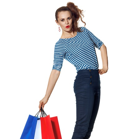 Shopping. The French way. cheerful trendy woman with shopping bags of the colours of the French flag isolated on white background