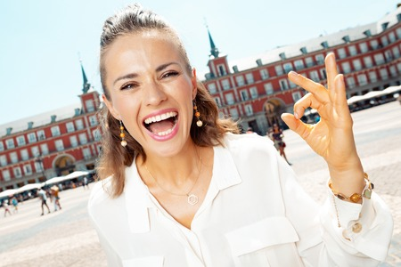 smiling trendy woman at Plaza Mayor showing ok gesture
