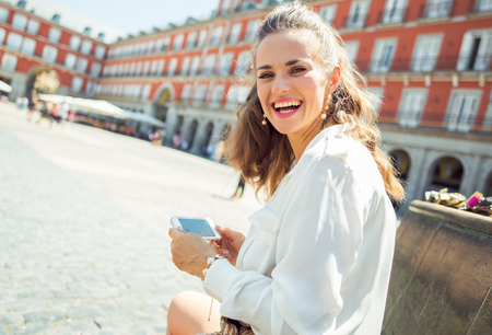 smiling modern woman at Plaza Mayor writing sms