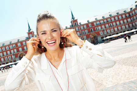 happy trendy tourist woman at Plaza Mayor listening to an audio guide