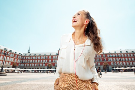 smiling young woman at Plaza Mayor looking into the distance and listening to an audio guide Sajtókép