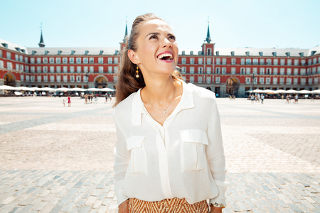 smiling modern tourist woman at Plaza Mayor exploring attractions
