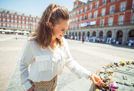 smiling modern tourist woman at Plaza Mayor viewing love locks Editorial