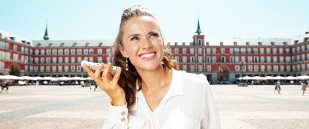 smiling young traveller woman at Plaza Mayor listening to an audio guide on smartphone