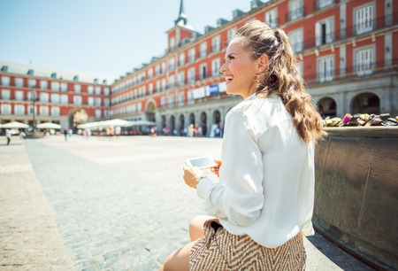 smiling young woman at Plaza Mayor writing sms