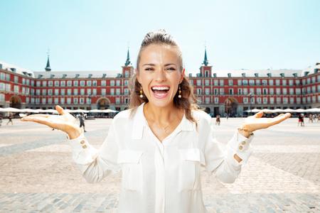 happy elegant traveller woman at Plaza Mayor presenting something on empty palm Editorial