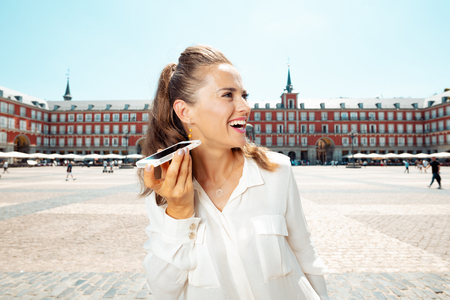 happy young tourist woman at Plaza Mayor listening to an audio guide on smartphone Sajtókép