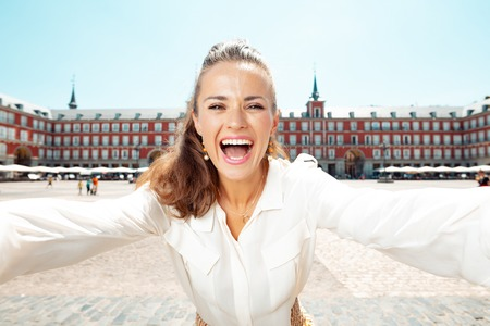 happy elegant tourist woman at Plaza Mayor taking selfie